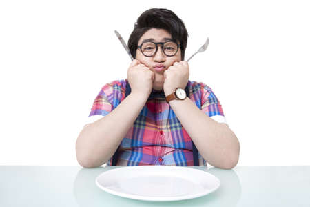 Worried overweight young man with empty plate LANG_EVOIMAGES