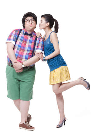 Happy overweight man and girlfriend kissing LANG_EVOIMAGES