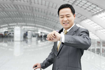 Mature businessman checking the time in airport lobby