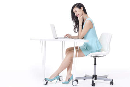 Fashionable businesswoman using laptop in office