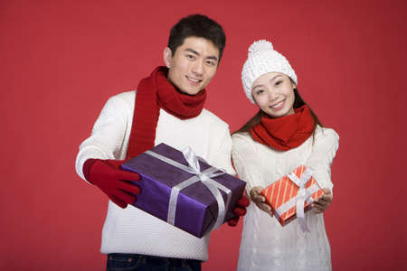 Young couple with holiday gifts LANG_EVOIMAGES