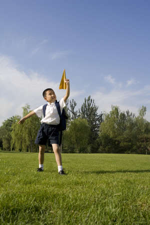 Boy playing with a paper airplane LANG_EVOIMAGES