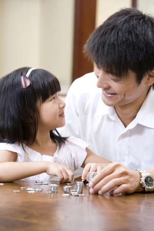 looking for love: Father and daughter counting coins