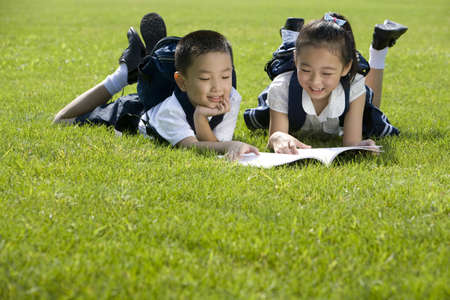 Elementary school students reading on the grass