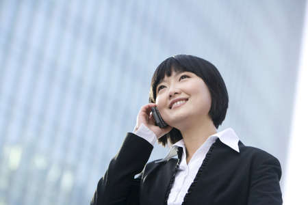 world at your fingertips: Businesswoman using cellphone LANG_EVOIMAGES