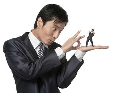 flicking: Businessman holding little figure LANG_EVOIMAGES