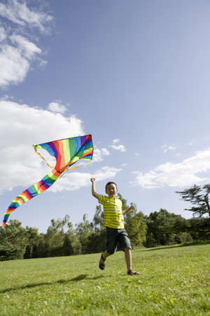 Young boy running with kite outdoors