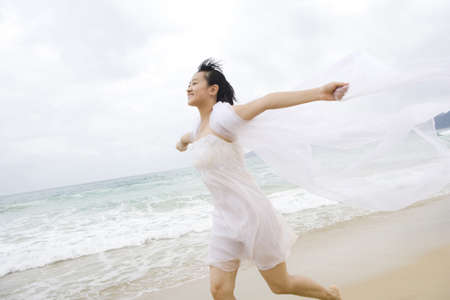 climas: Portrait of a young woman running along the beach