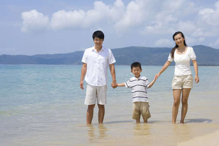 ankle deep in water: Young family on the beach