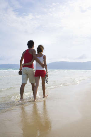 ankle deep in water: Young couple on a romantic walk along the beach