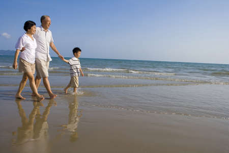 ankle deep in water:  Grandparents and grandson walking along the beach