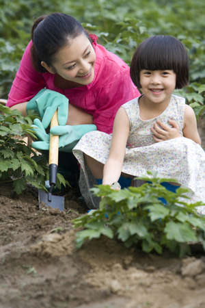 dug well: Mother and daughter gardening LANG_EVOIMAGES