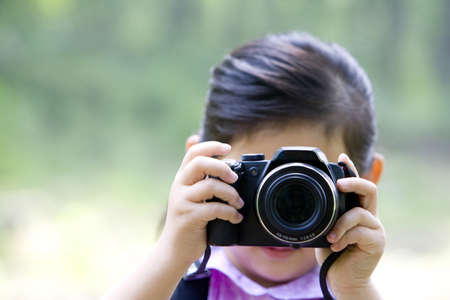 Little girl taking photos in nature