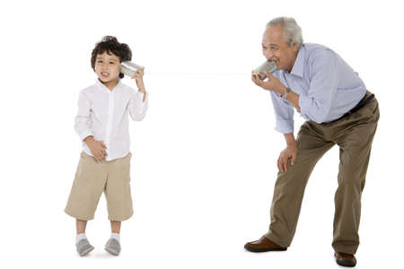 resourceful: Grandfather and grandson playing with a tin-phone