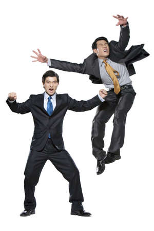 punched out: Two businessmen fighting on white background