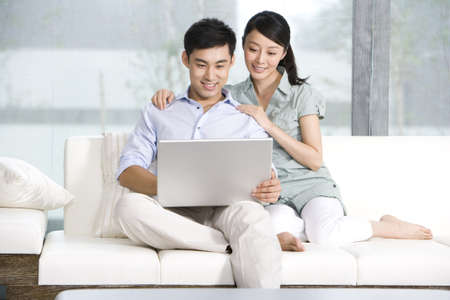 sit down: Portrait of a couple using a laptop at home