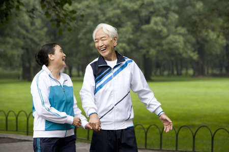 Senior Couple Walking Hand-In-Hand Through a Park LANG_EVOIMAGES