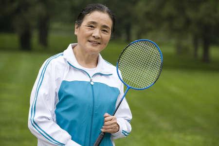Senior Woman Holding Badminton Racket in a Park LANG_EVOIMAGES