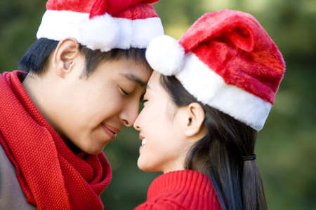 love at first sight: Young Couple Rub Noses while Wearing Santa Hats LANG_EVOIMAGES