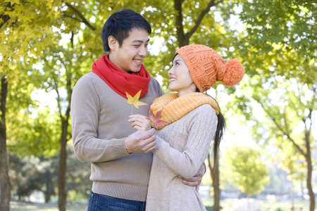 love at first sight: Young Couple in a Park in Autumn Holding Maple Leaves LANG_EVOIMAGES