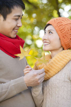 love at first sight: Young Couple in a Park in Autumn Holding Golden Maple Leaves