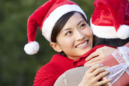 Young Woman Embraces Young Man while Holding Christmas Gift