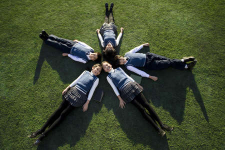 Five classmates lying in a star shape on grass LANG_EVOIMAGES