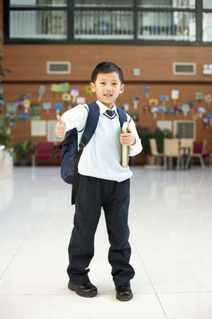 only boys: Young student giving a thumbs up while holding a book LANG_EVOIMAGES