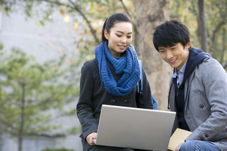 A young man and woman using a laptop together on a park bench