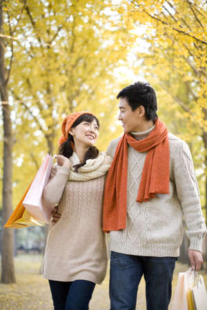 love at first sight: Young Couple in a Park with Shopping Bags