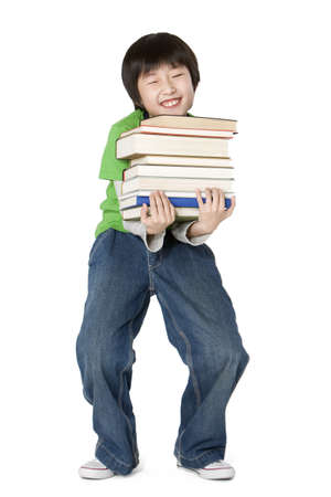 Young boy carrying a large stack of books