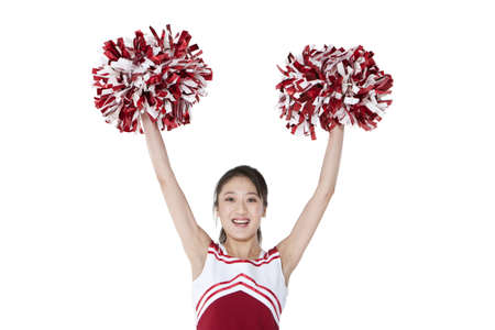 Cheerleader in action with her pom-poms LANG_EVOIMAGES