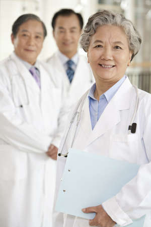 Senior Female Doctor with Two Doctors in Background LANG_EVOIMAGES