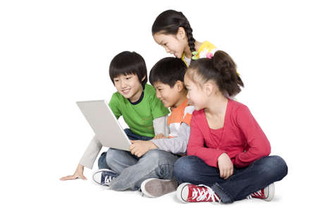 A group of children using a laptop together