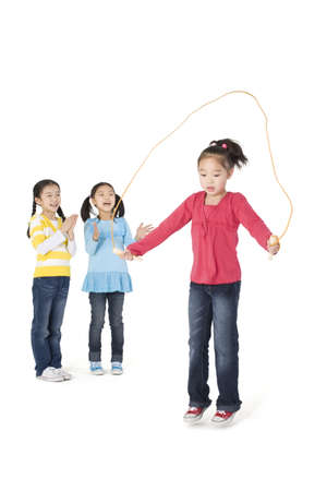 Two girls cheering their friend as she jump ropes