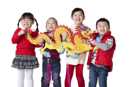 Four Chinese children holding Chinese dragon aloft