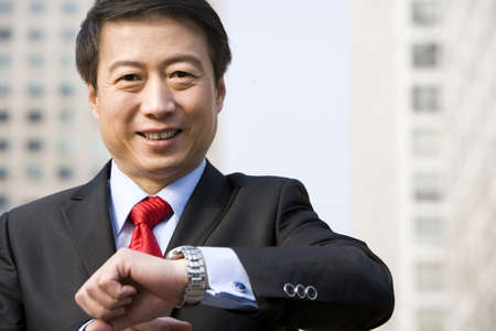 business: Portrait of a businessman checking his watch