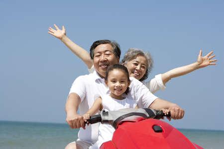 Grandparents and Granddaughter Riding on a Jet Ski LANG_EVOIMAGES