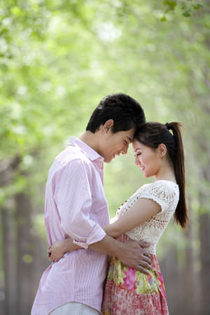 Happy Young Couple Embracing at the Park LANG_EVOIMAGES