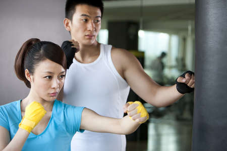 Young Man and Young Woman Punching Punching Bag LANG_EVOIMAGES