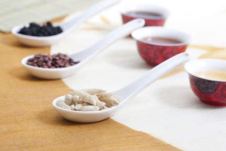 enano: Medicina china en cucharas descansando sobre tazas de té