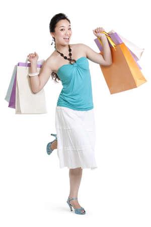indoor shot: Studio shot of a young woman carrying shopping bags