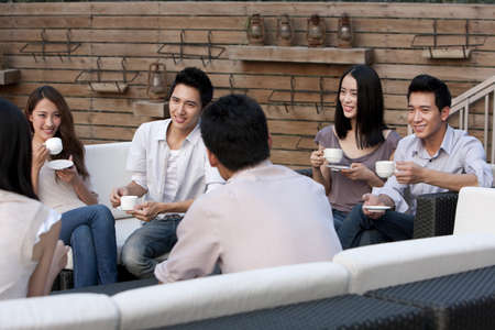 happy asian people: Friends Relaxing at an Outdoor Bar