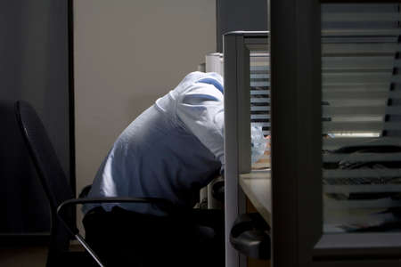 trapped: Young man lays head on desk in cubicle LANG_EVOIMAGES