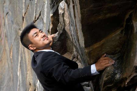 out of context: A businessman climbing a rock face