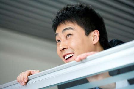 Man peeking over railing LANG_EVOIMAGES