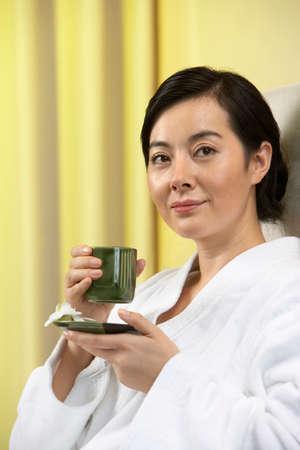 oriental bathrobe: Woman drinking tea at a spa