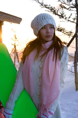 Young woman holding a snowboard LANG_EVOIMAGES