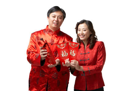 A couple holds gifts and a bottle of wine for Chinese New Year