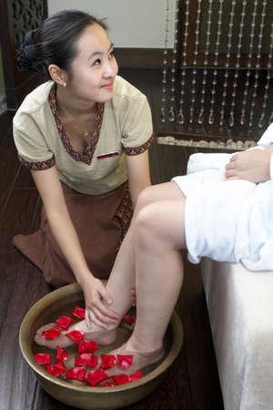 oriental bathrobe: Spa attendant washing a womans legs in a foot bath